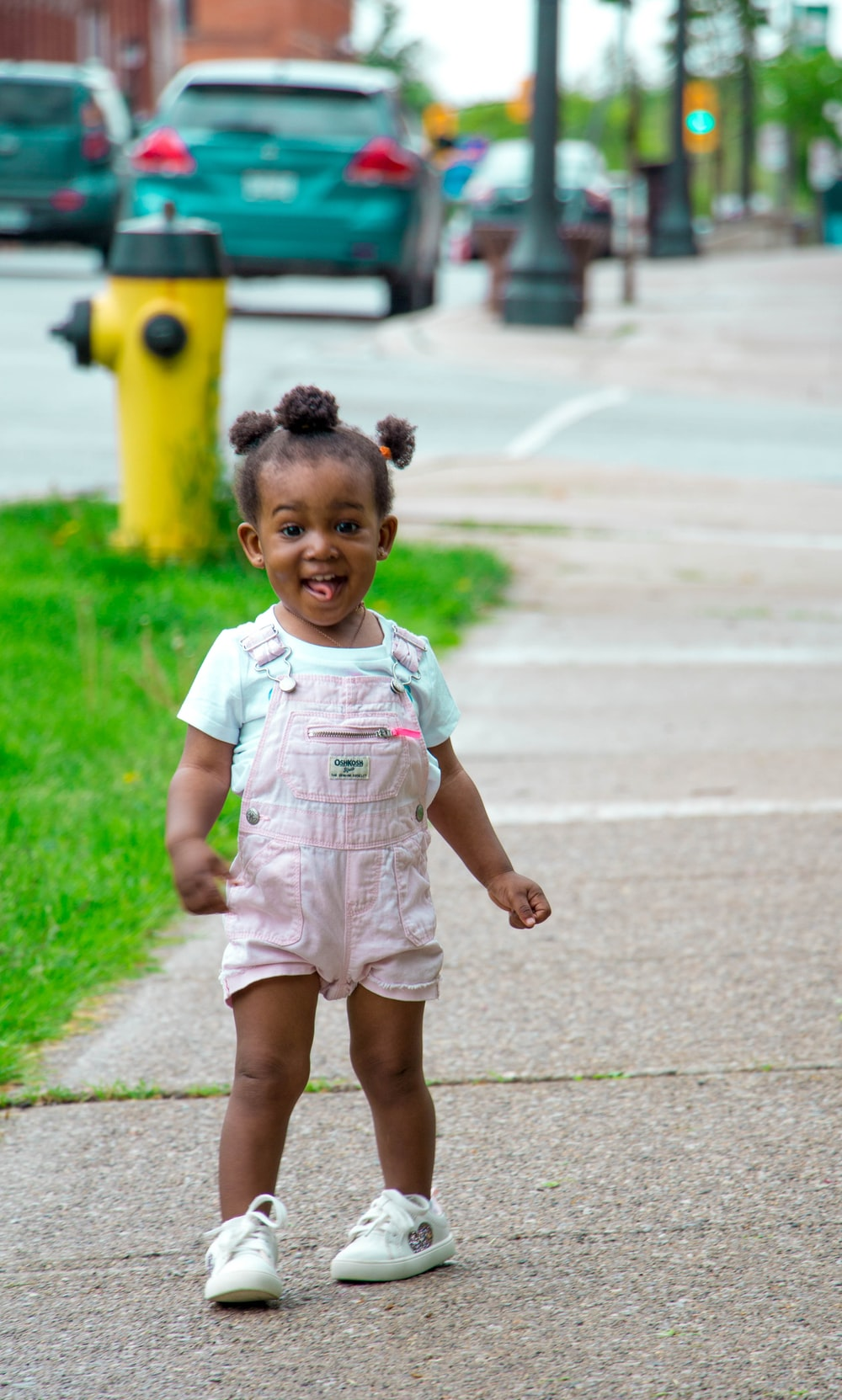 girl in pin k shortalls and white sneakers