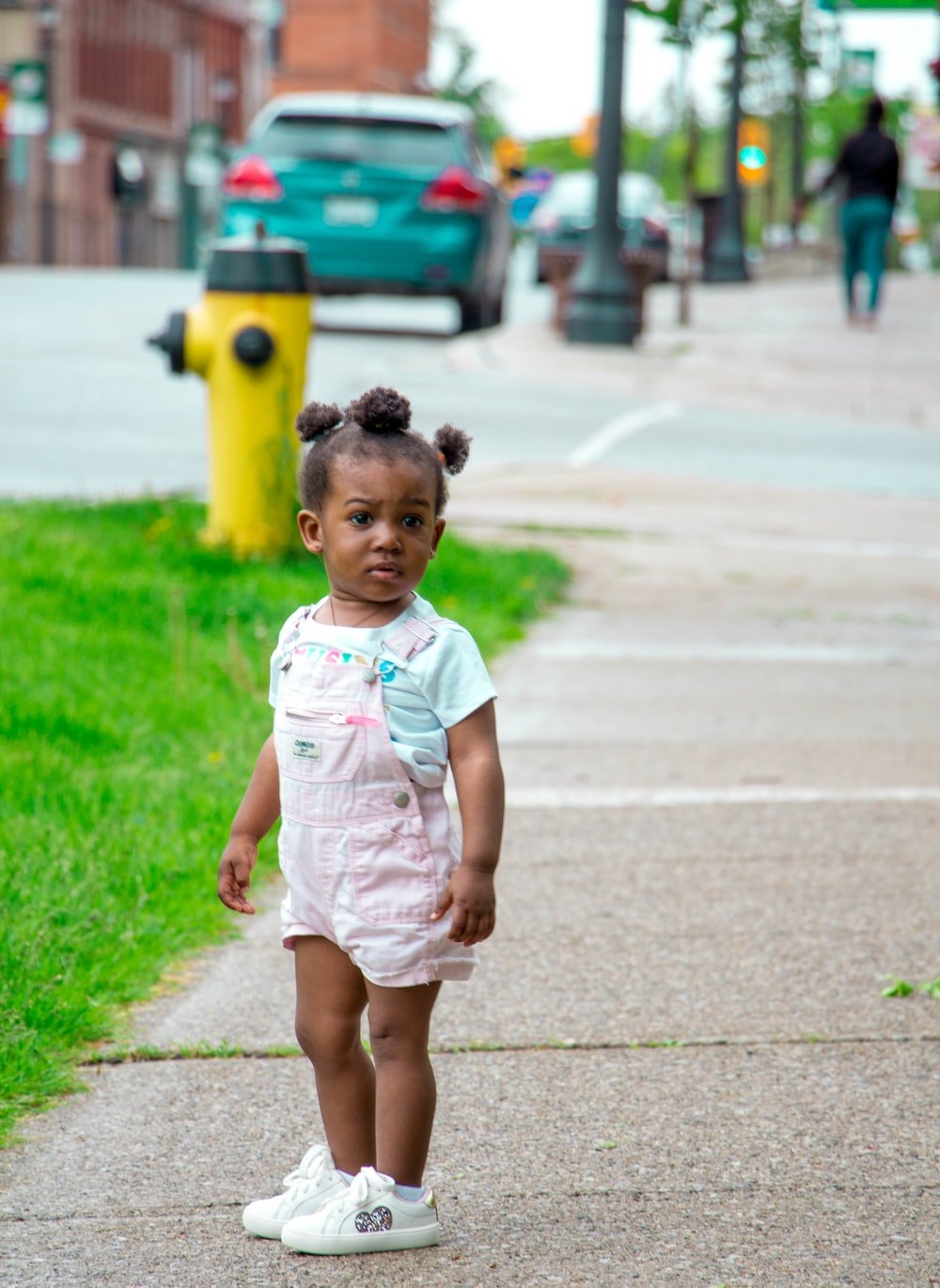 girl in pink shortalls and white sneakers standing on walkway