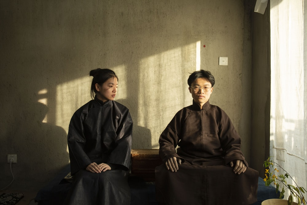 man and woman in robes by concrete wall at daytime