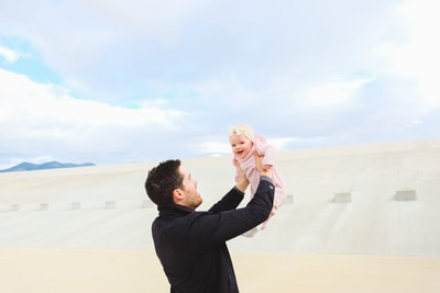 man carrying baby during daytime father's day teams background