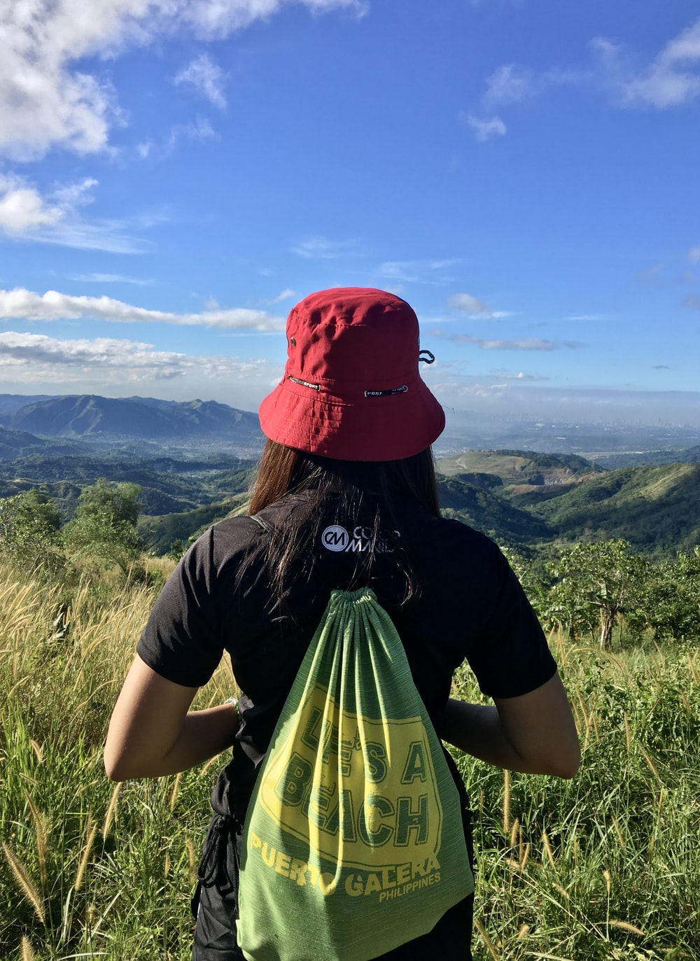 woman with bag facing mountains during daytime