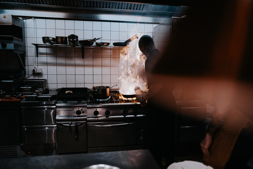 person doing cook inside kitchen
