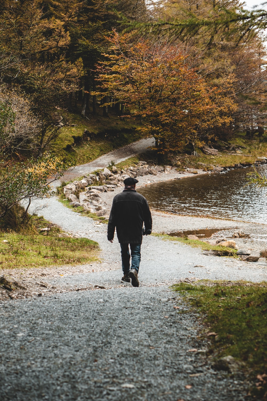person walking beside body of water