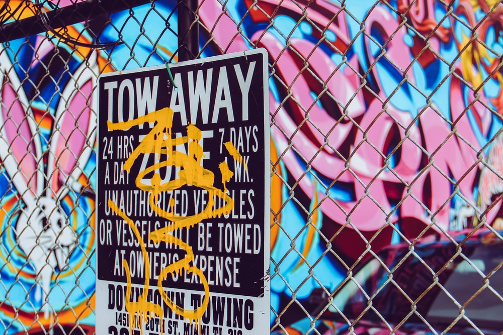 Tow Away signage on chain-link fence