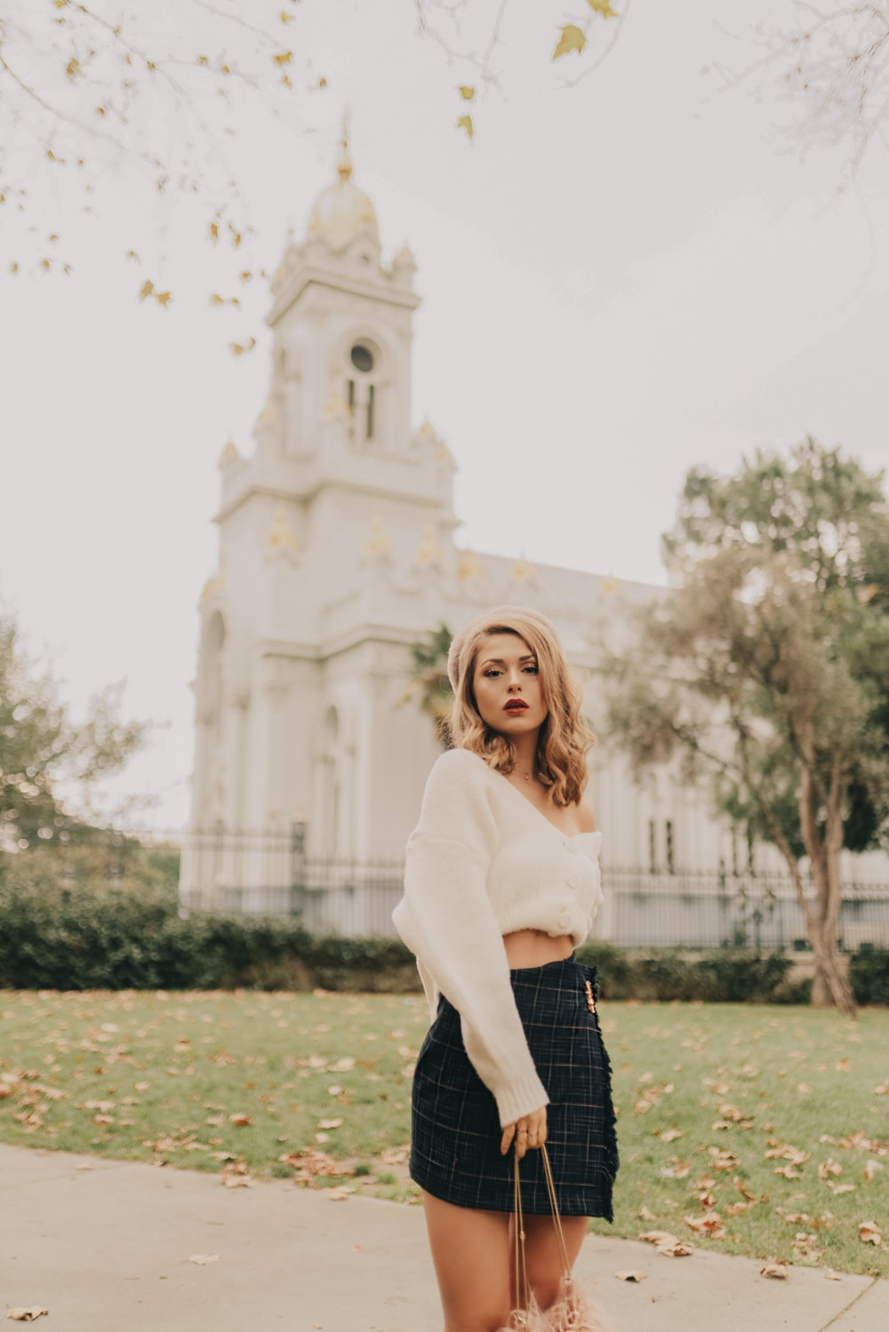 woman wearing white long-sleeved crop top standing near road viewing white church during daytime
