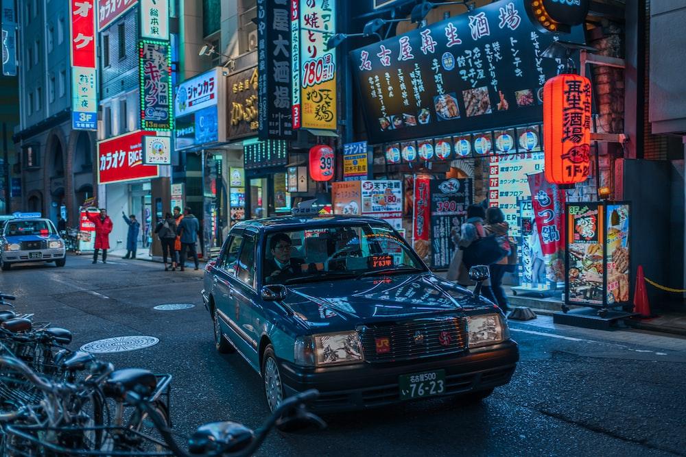 blue sedan on road at night