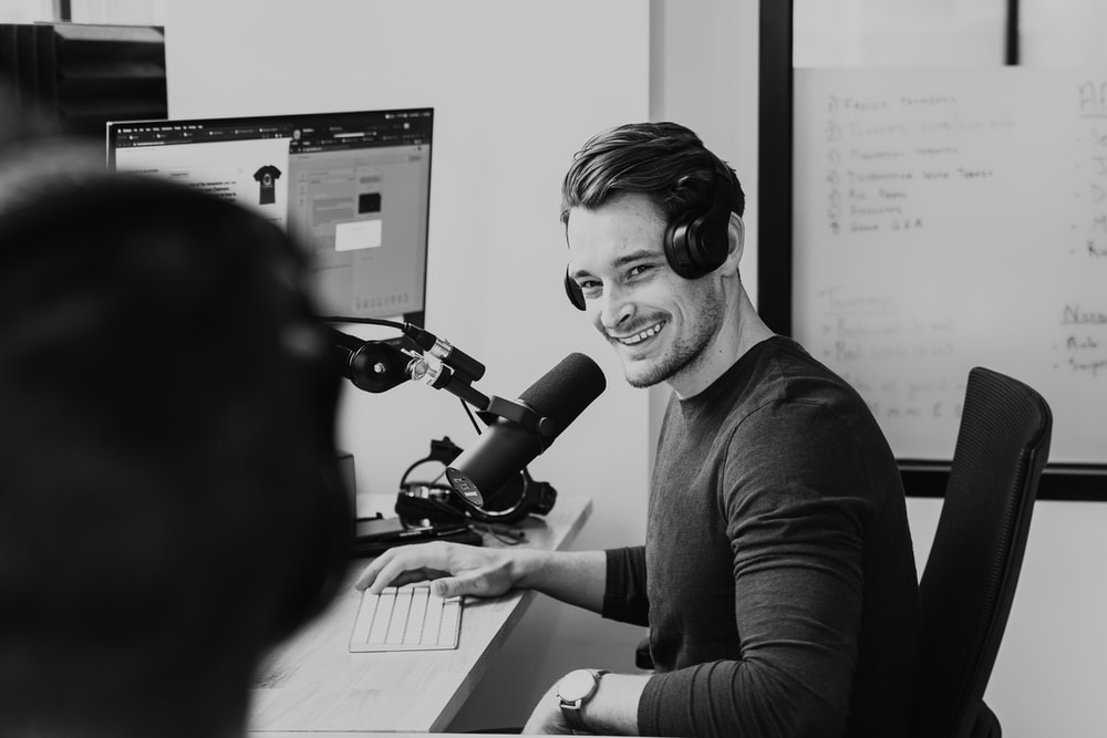 greyscale photo of man sitting by the table using headphones and microphone while smiling