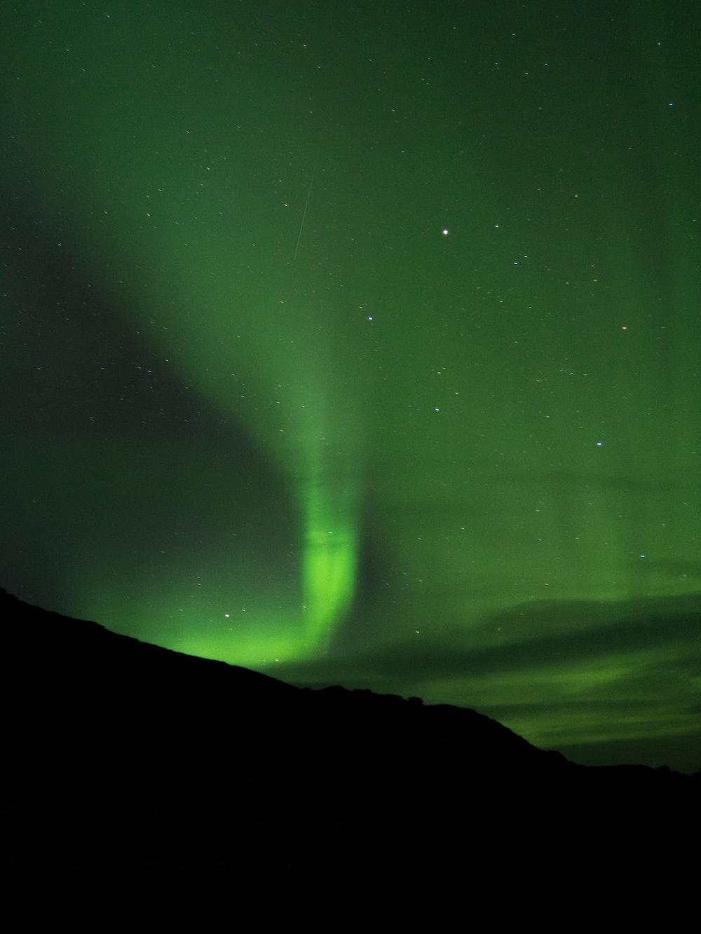 silhouette of mountain under Aurora borealis