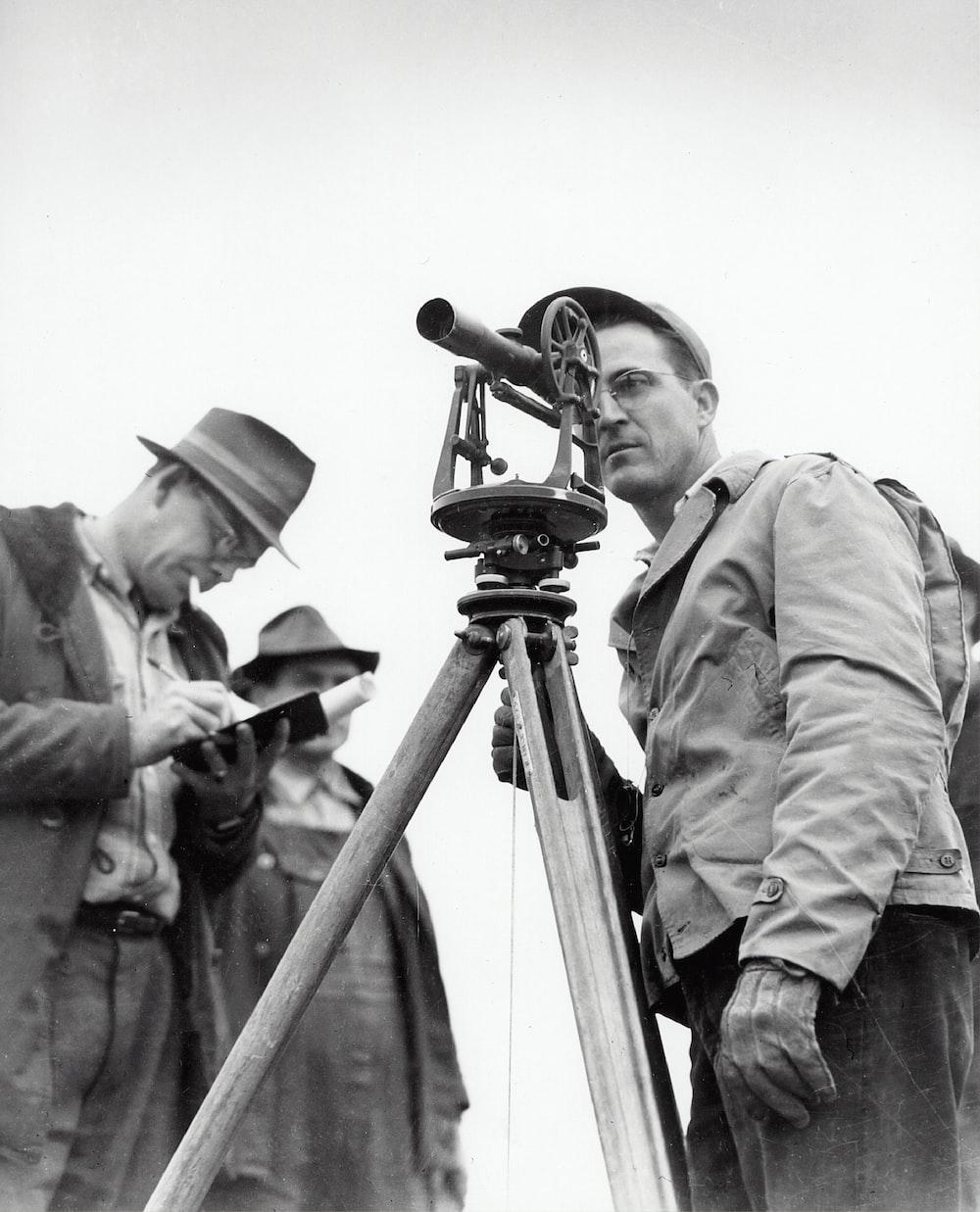 man looking at telescope