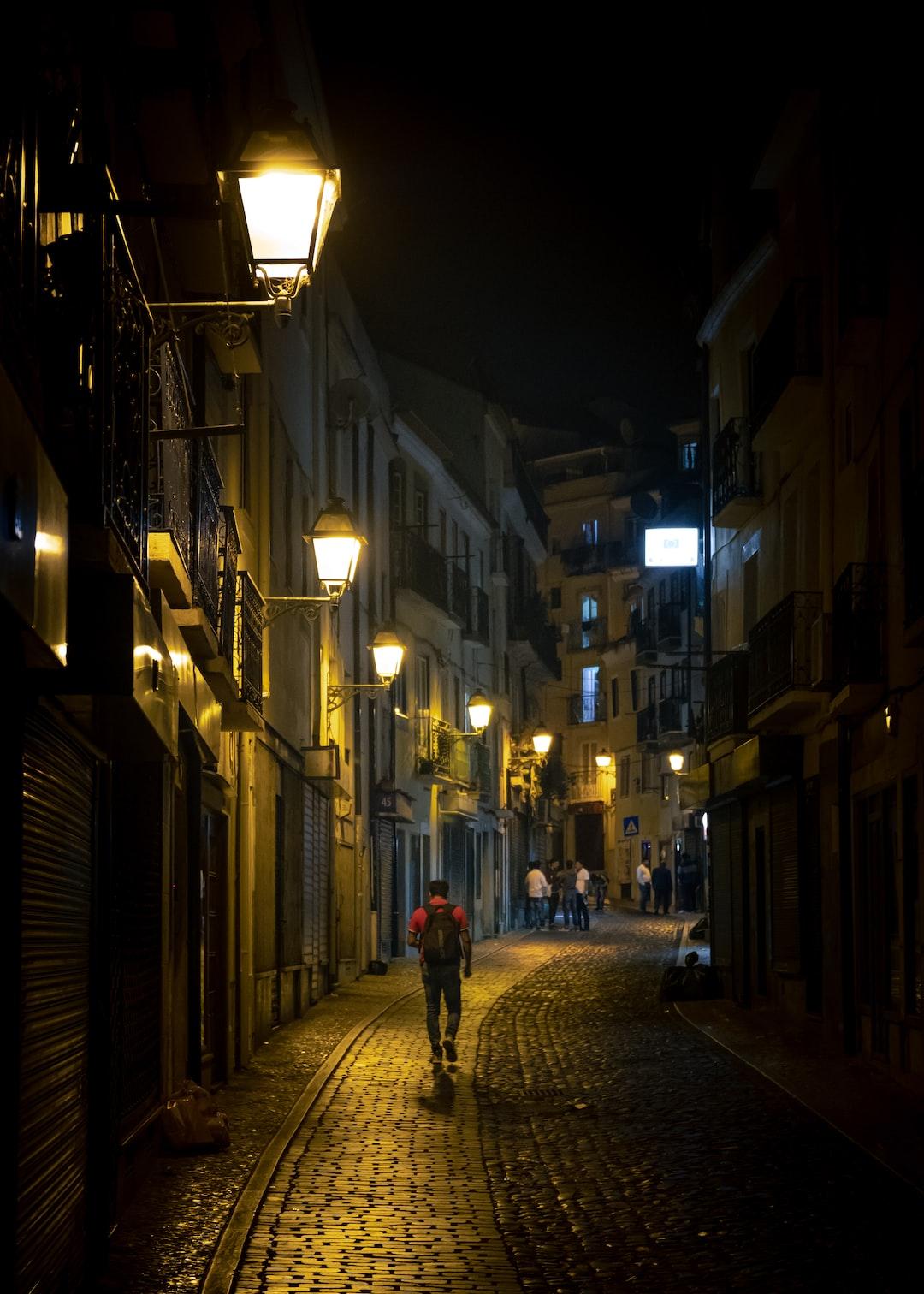 Man walking in a street in lisbon at night.