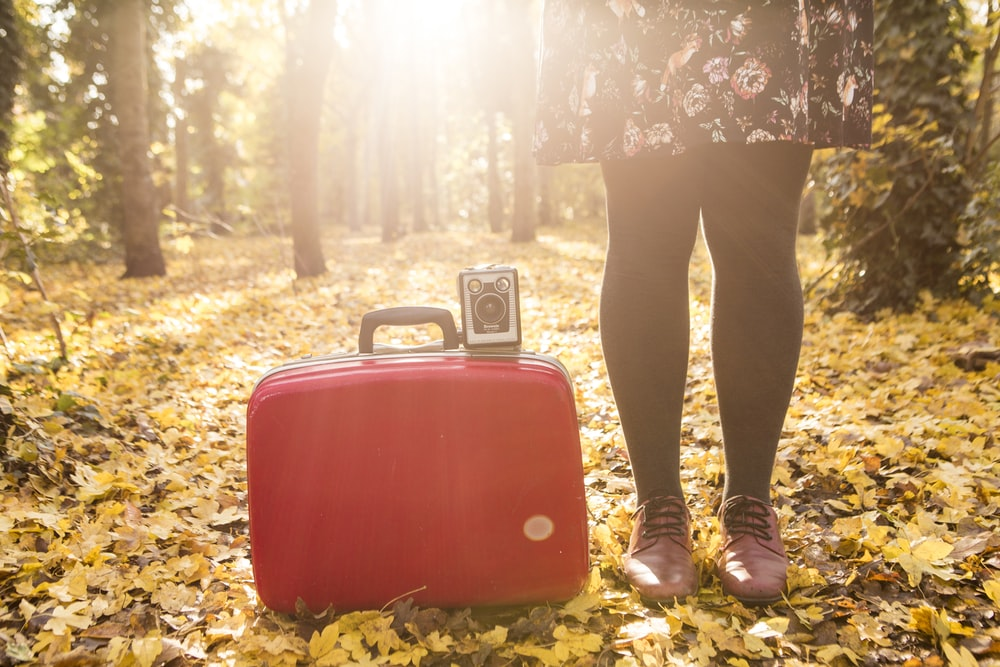 woman standing beside red suitcase and camera