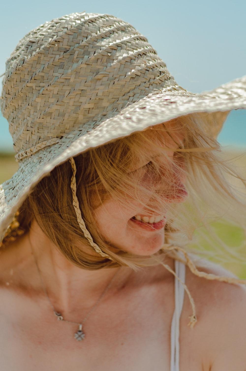 smiling woman wearing gray sun hat