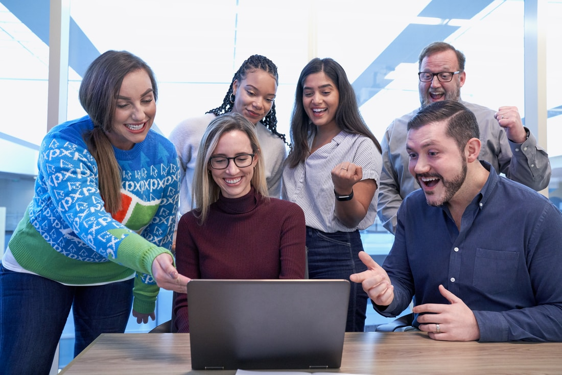 men and women sitting and standing while staring at laptop