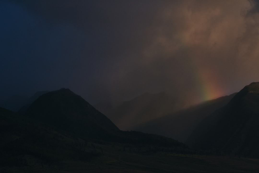 Rainbow and storm clouds over the West Maui Forest Reserve mountains near Lahaina, HI at sunset.