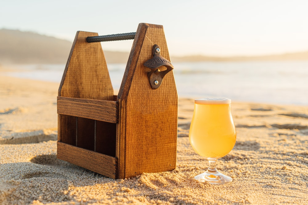 brown wooden tool box beside clear wine glass on sand
