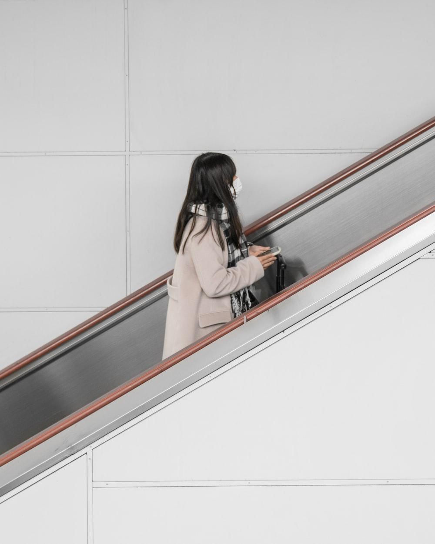 woman in gray coat in escalator