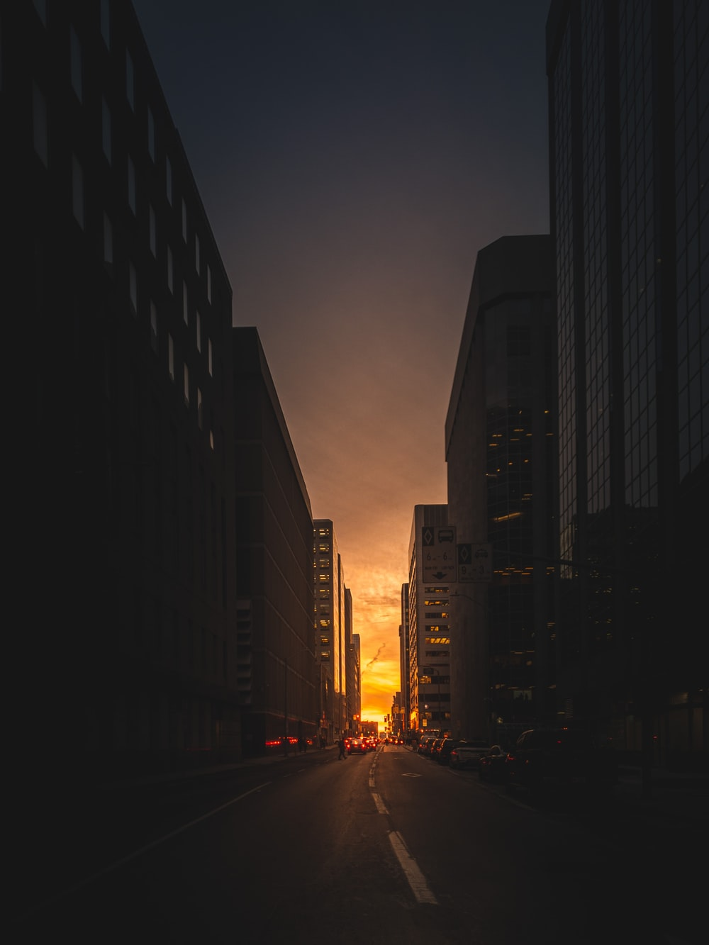 view photography of road between high rise building during sunrise