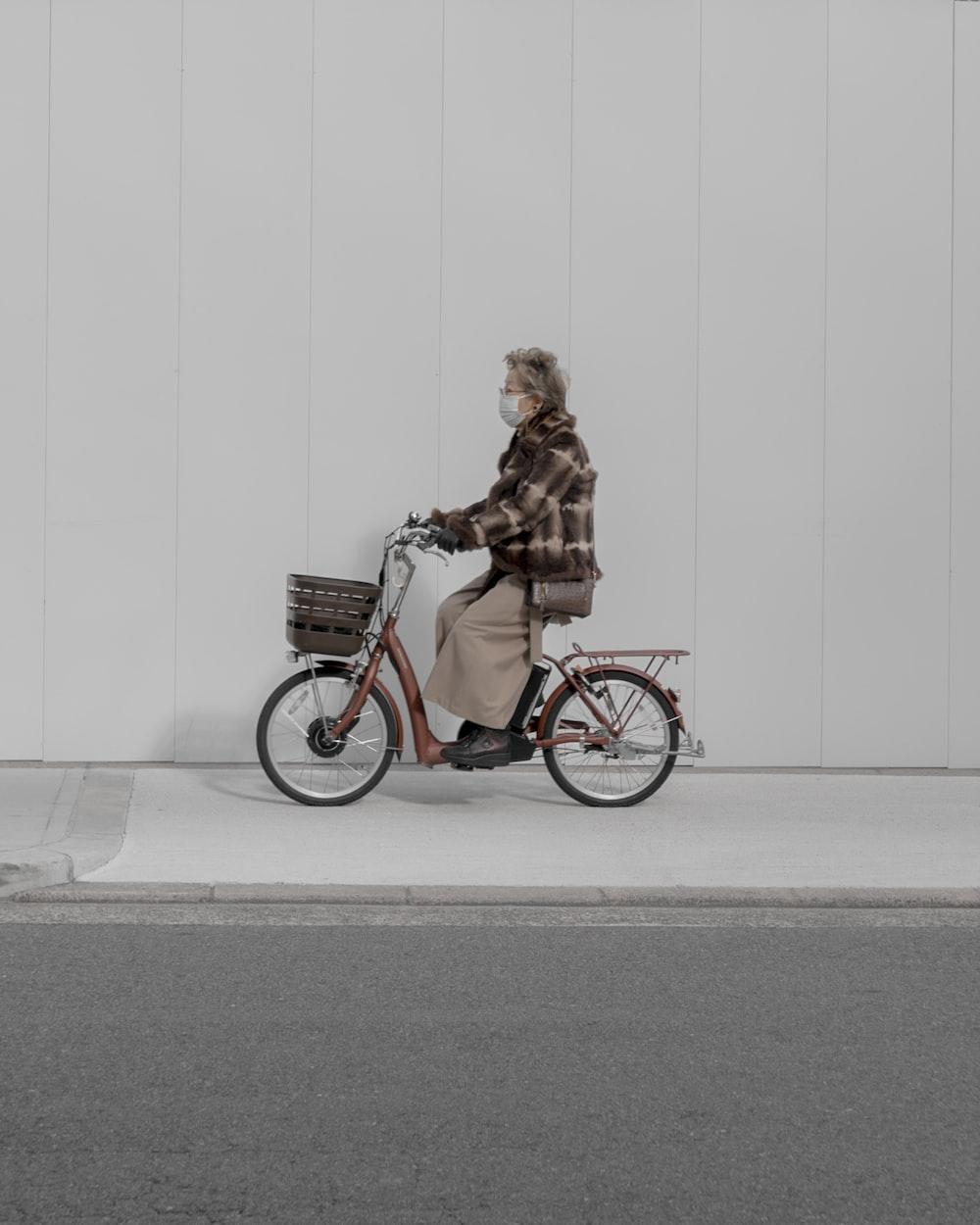 woman riding city bike near wall and road
