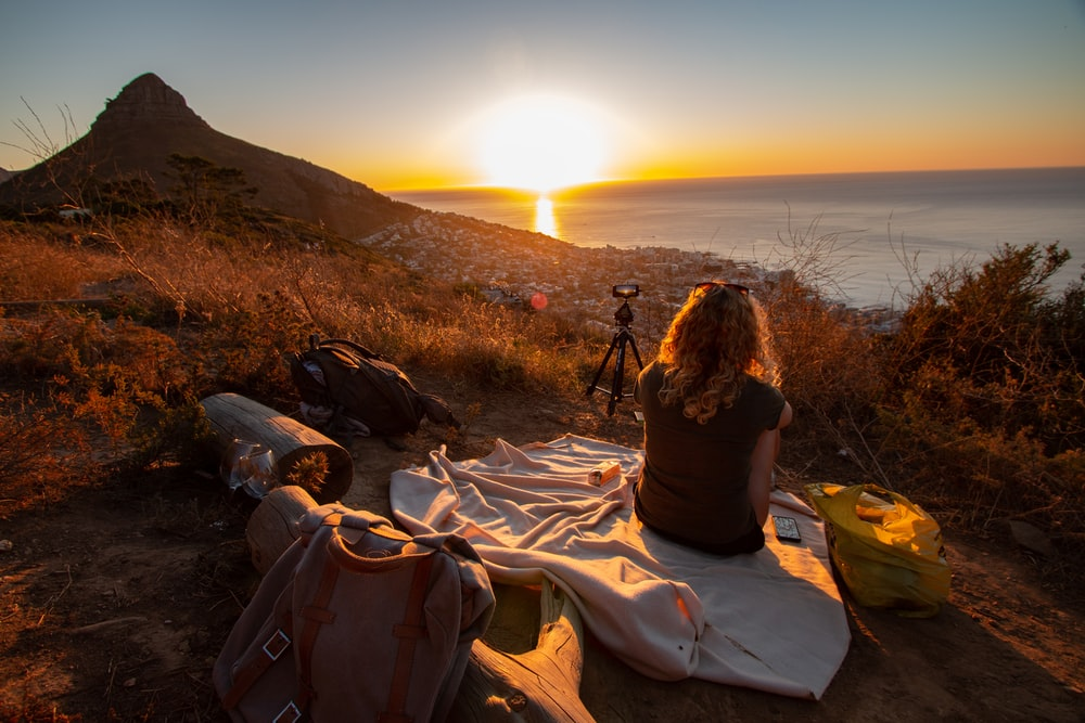 woman sitting on blanket near sea and mountain during dawn