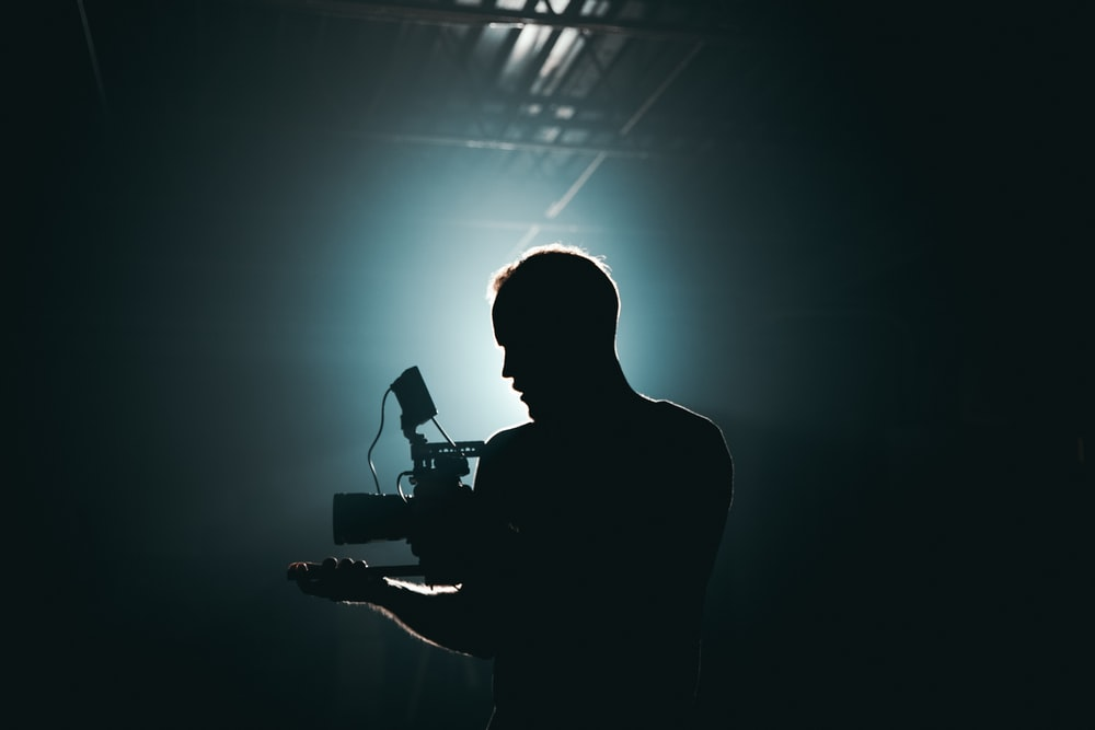 silhouette photography of man holding camera