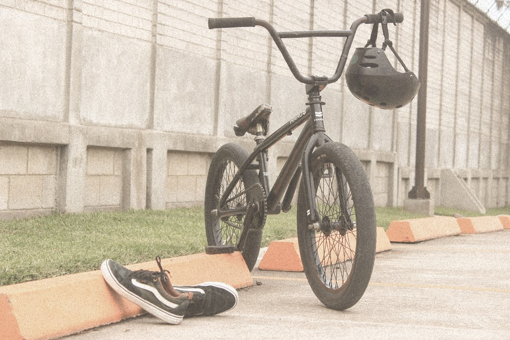 pair of black VANS Original shoes beside BMX bike