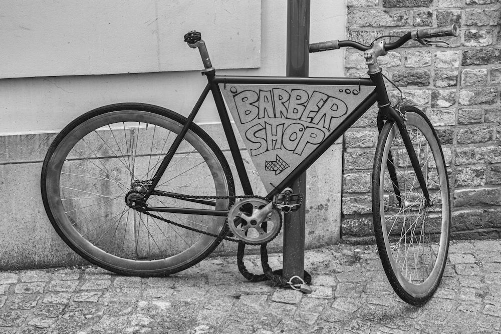 black rigid bike parked beside wall