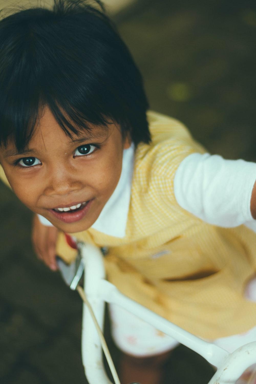 boy wearing white and yellow dress