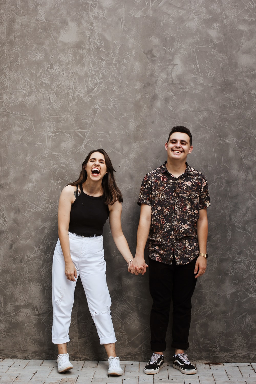 woman and man holding hands near grey wall
