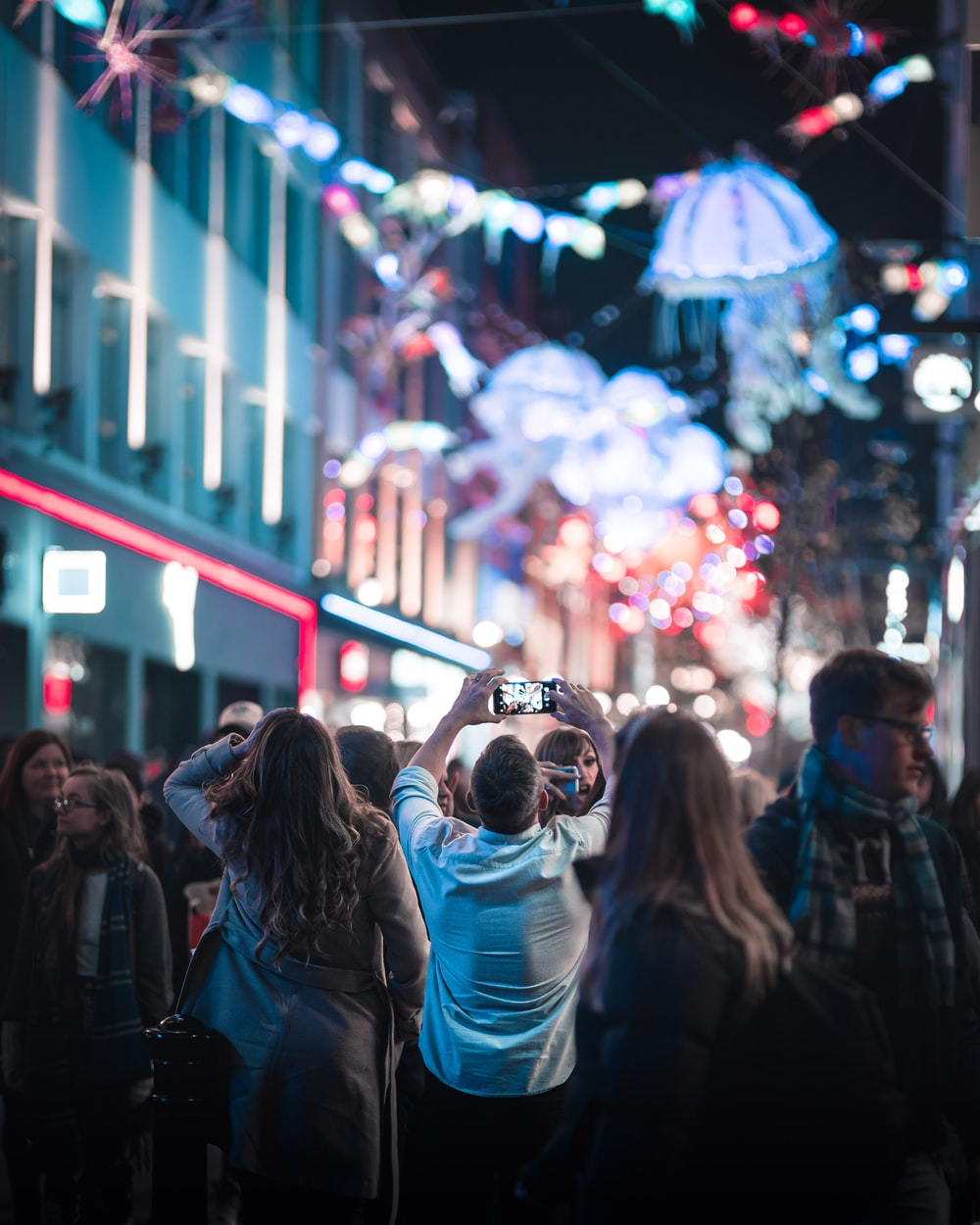 people in city with lights at night