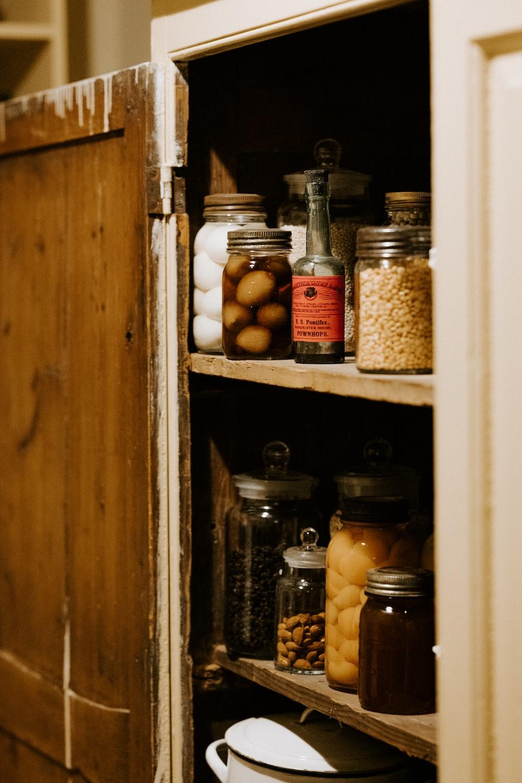 preserve jars on brown wooden shelf