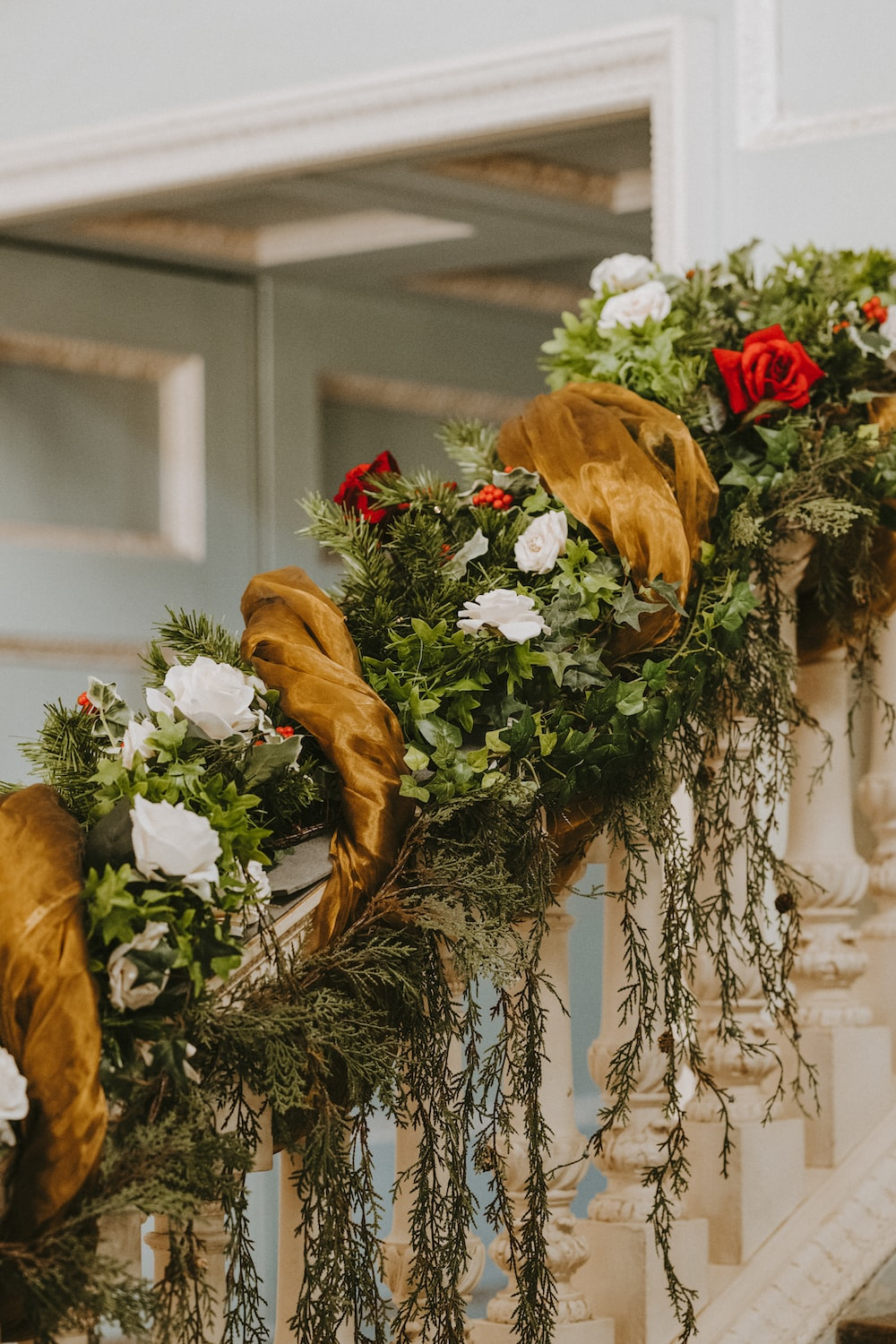 green wreath with red and white rose on handrail