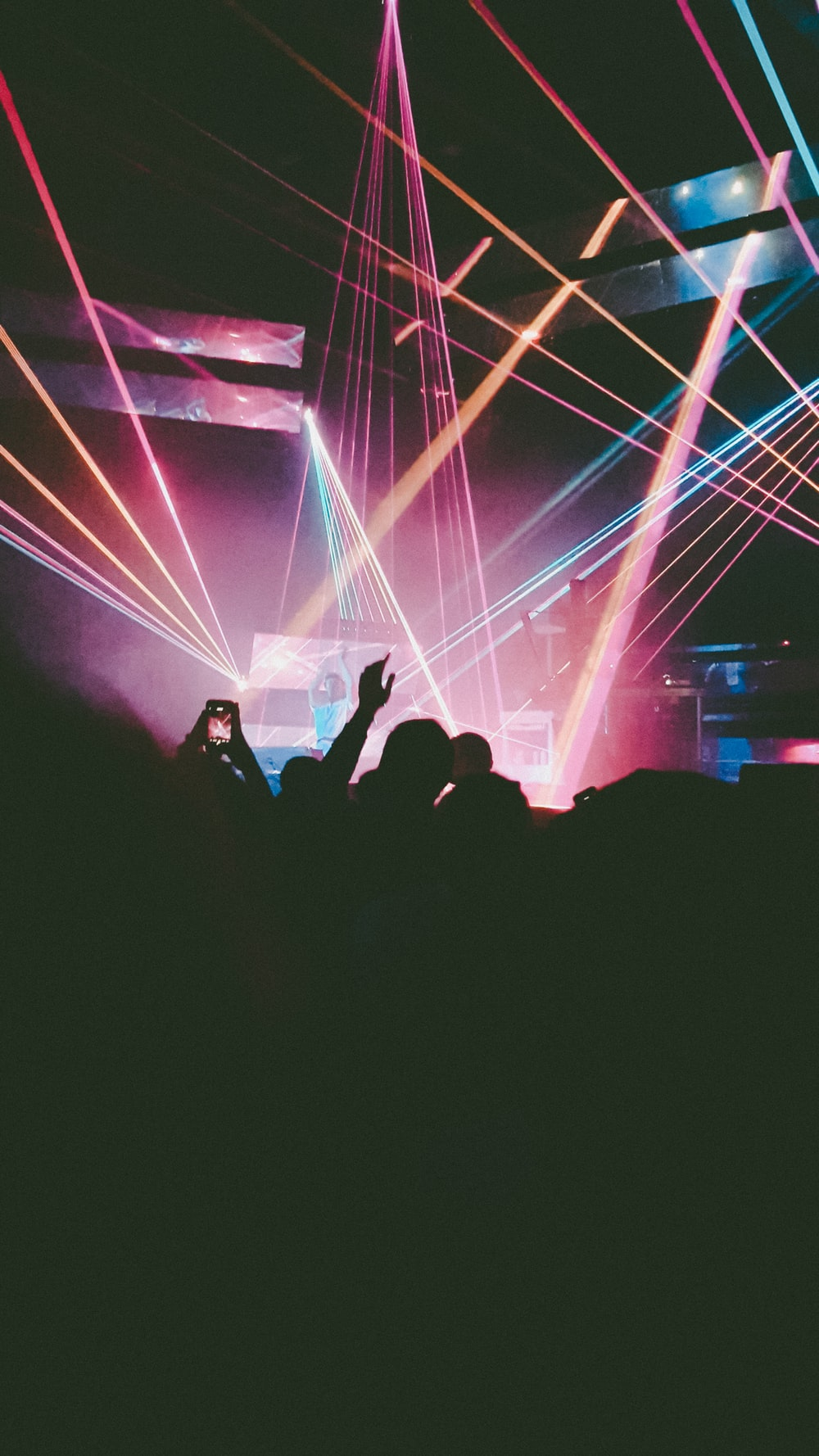people performing on stage with lights in front of crowd