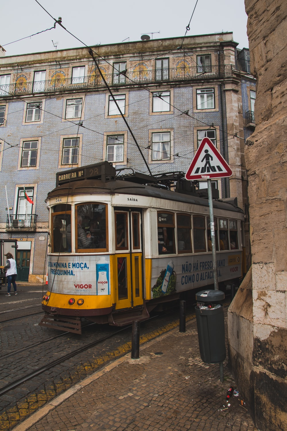 cable train beside the sidewalk and buildings during day
