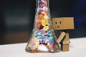 humanoid box toy standing on glass bottle