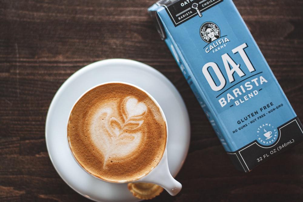 cup of latte beside oat barista box