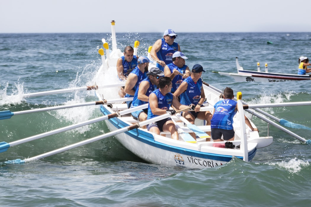 Teamwork. Align goals. Rowing boat together.