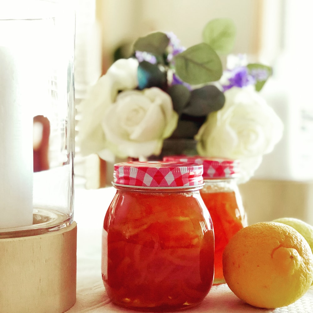 two glass jars near vase of flowers