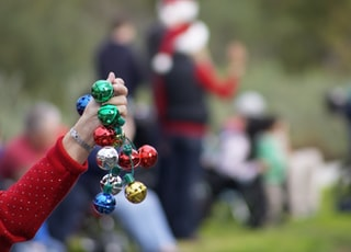 person holding multicolored baubles