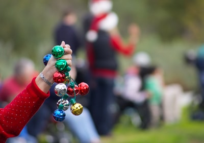 person holding multicolored baubles jingle bells teams background