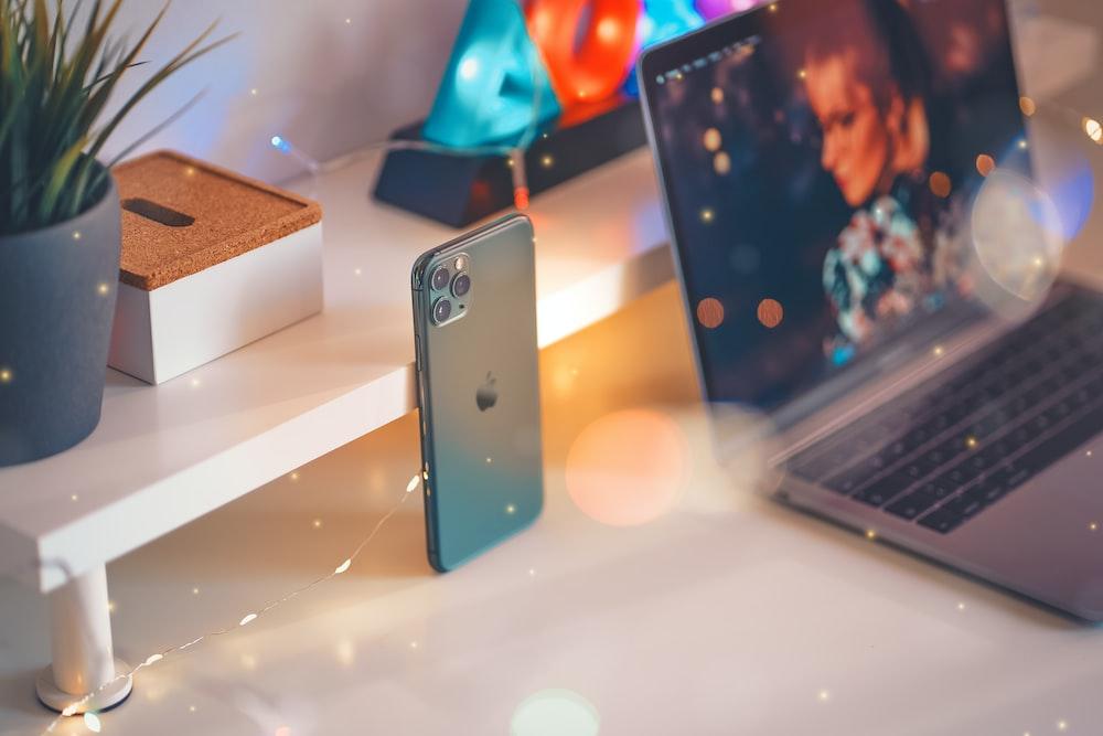 silver iPhone 11 near MacBook Pro