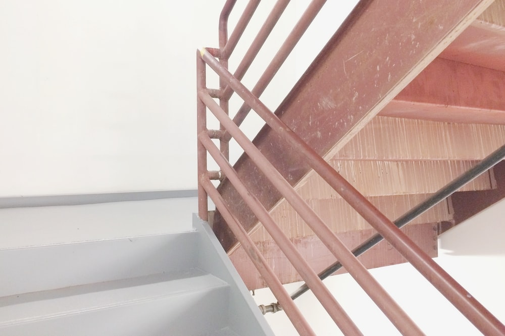 brown and white staircase with railing