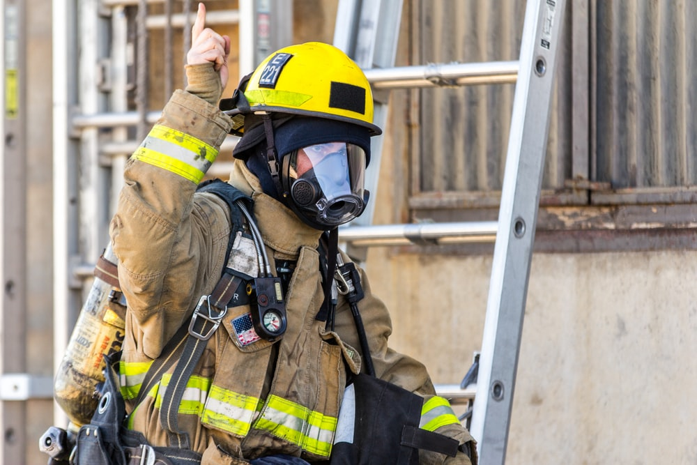 fireman wearing mask standing and about to climb on ladder