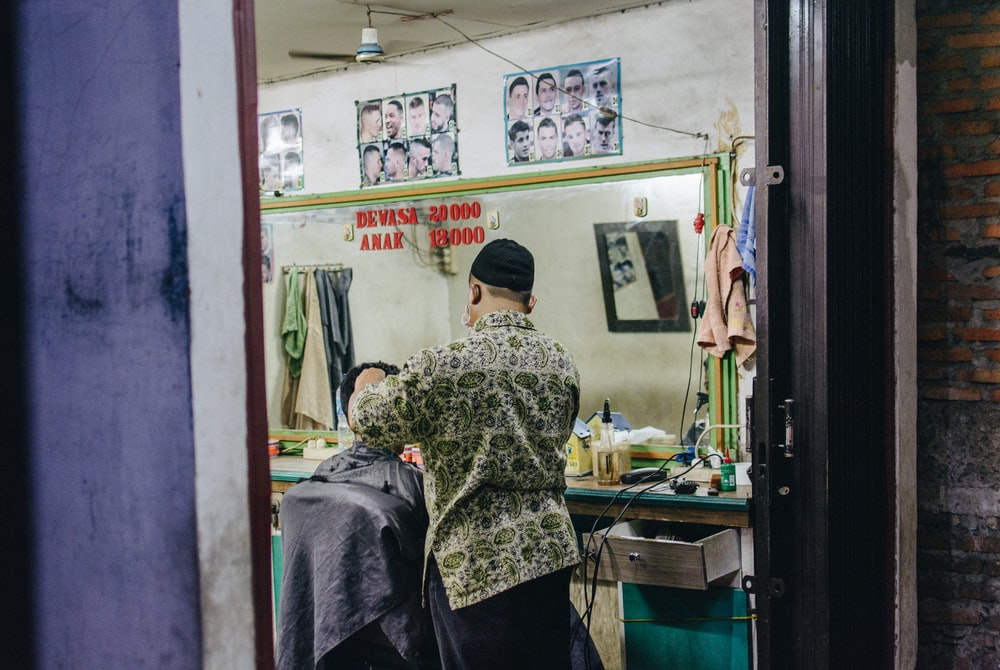 man standing while cutting hair of another person sitting