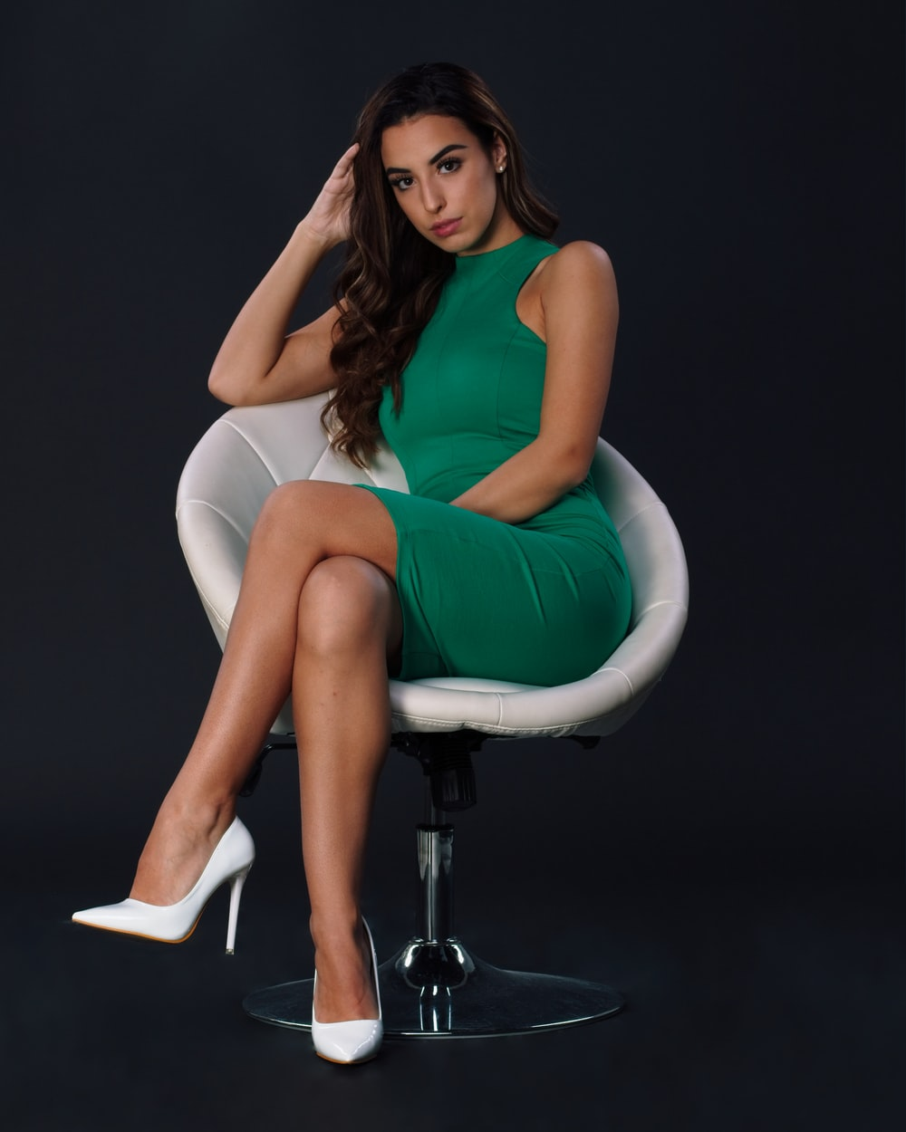 woman wearing green sleeveless dress sitting with crossed legs