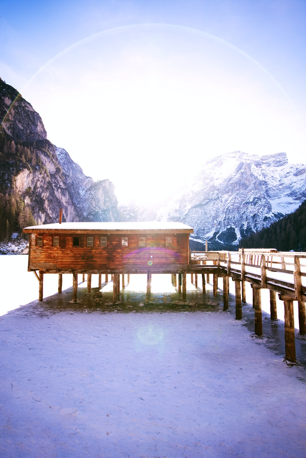 shallow focus photo of cabin near snow covered mountain