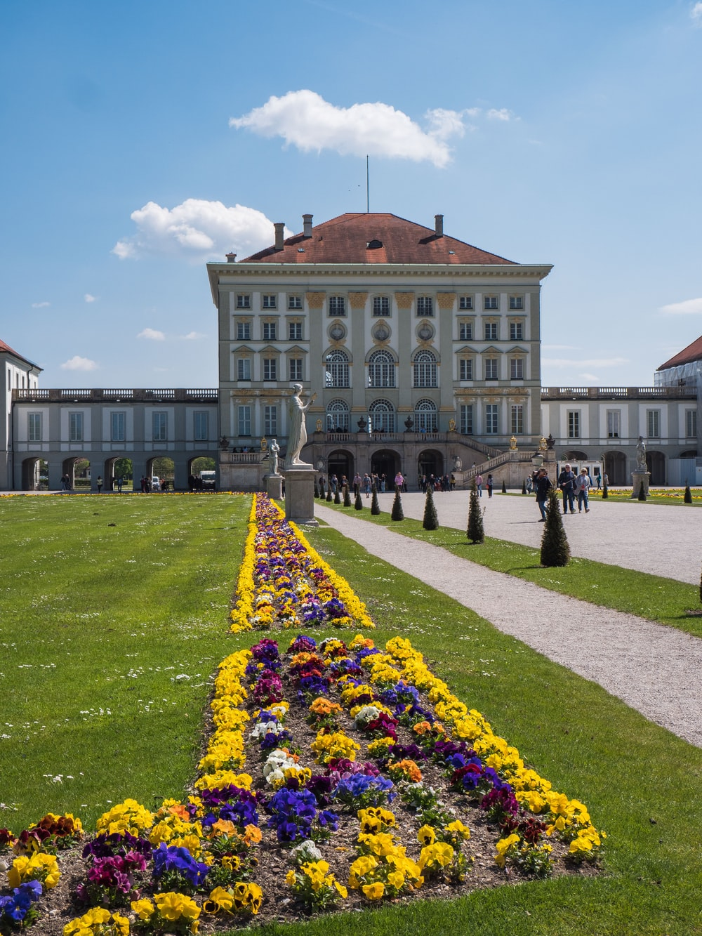 people walking near Nymphenburg Palace in Munich, Germany under blue and white sky