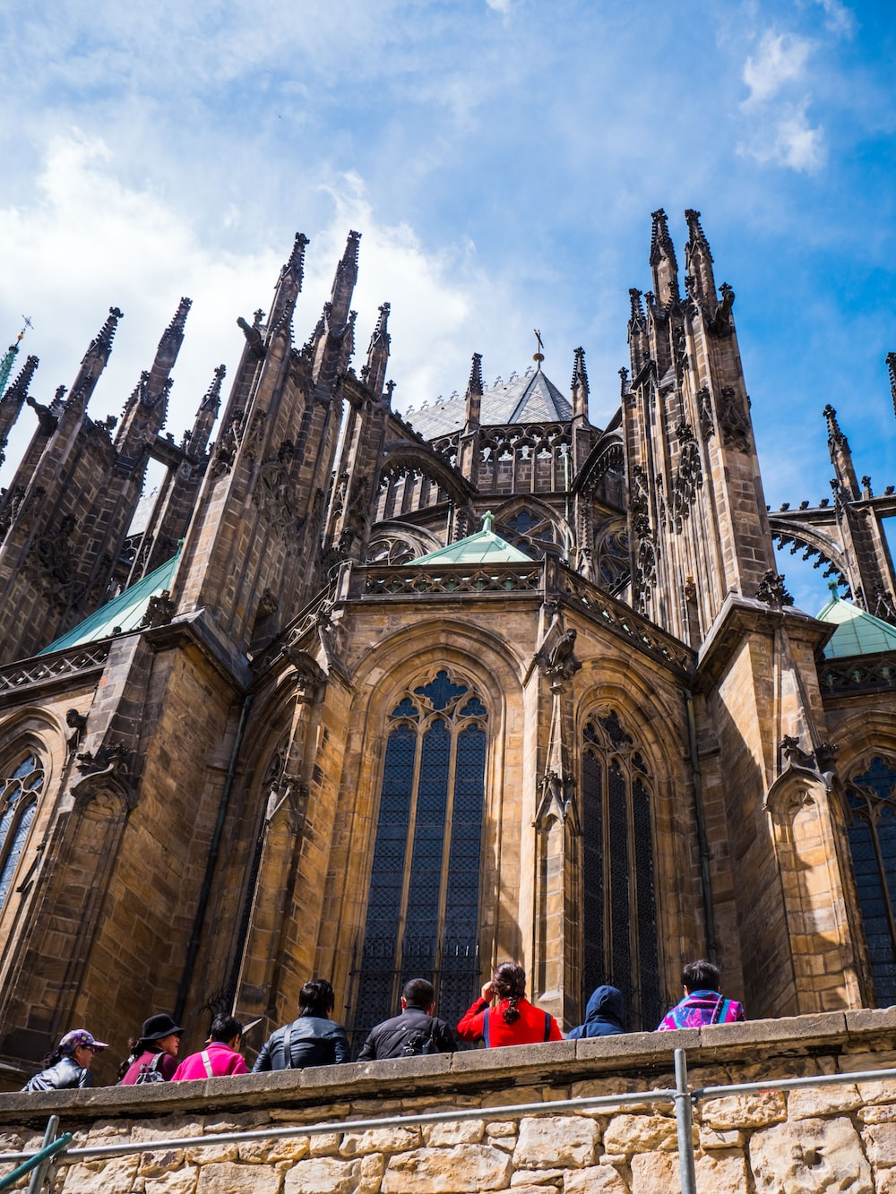 people standing near St. Vitus Cathedral in Prague, Czechia under blue and white sky