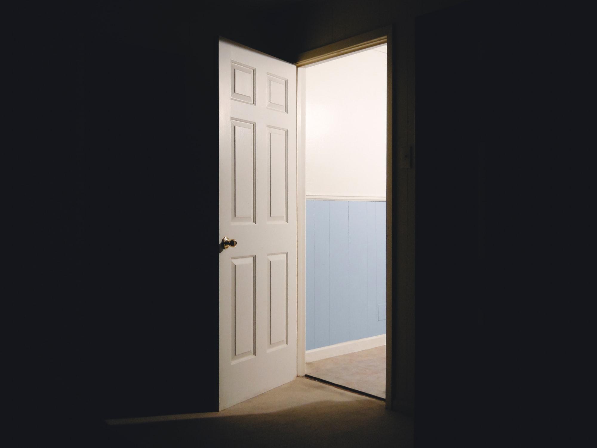 An open door allowing light to shine into a dark room  | Please check out my blog at: matthewtrader.com/unsplash