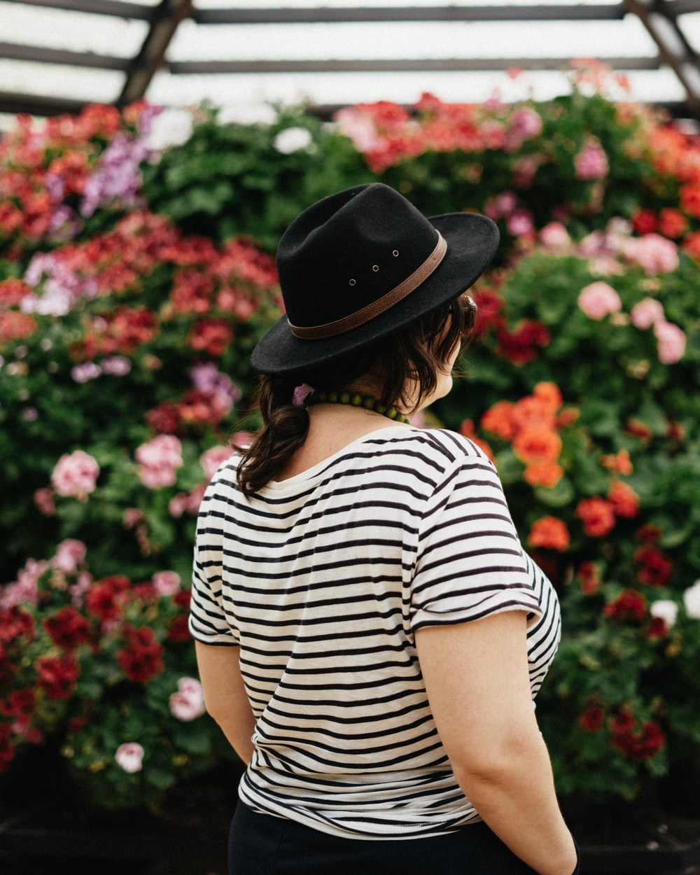 selective focus photo of woman facing on the flower