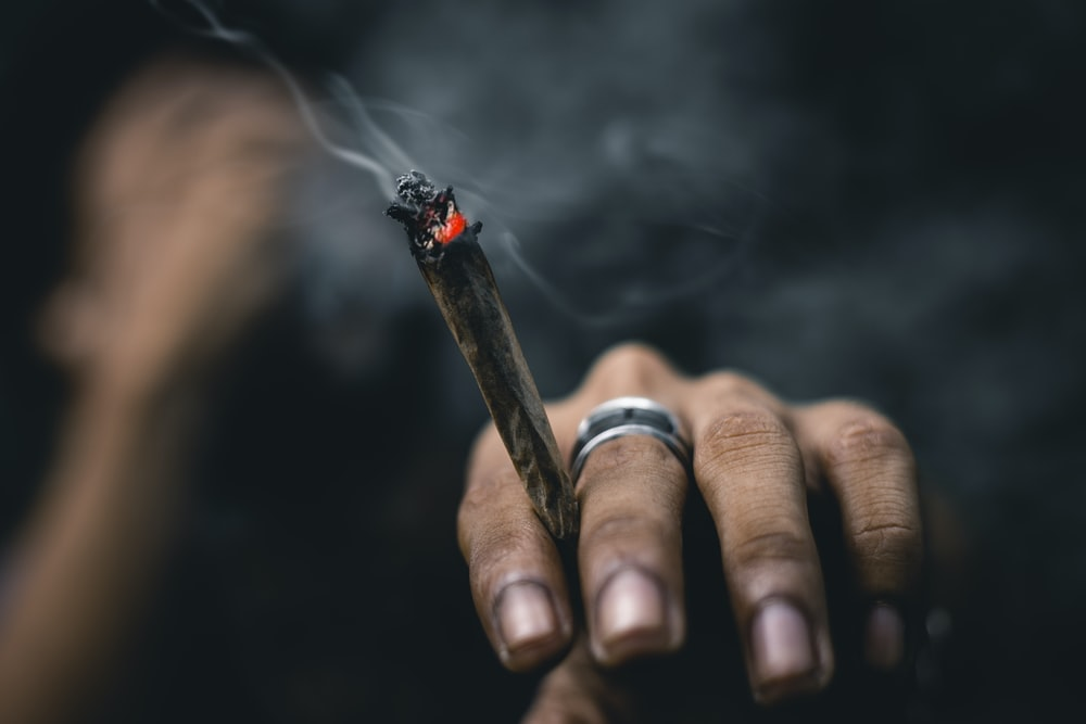 person wearing ring and holding blunt